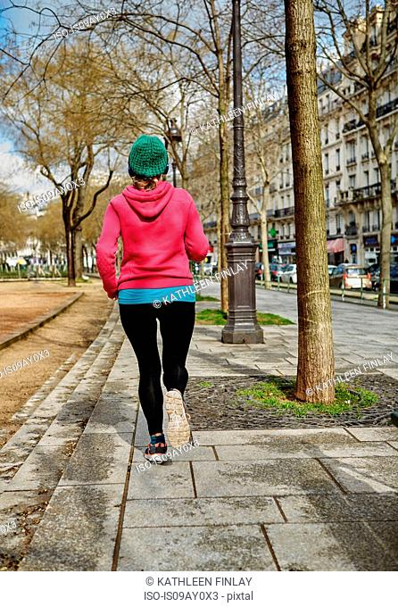 Rear view of woman jogging in street