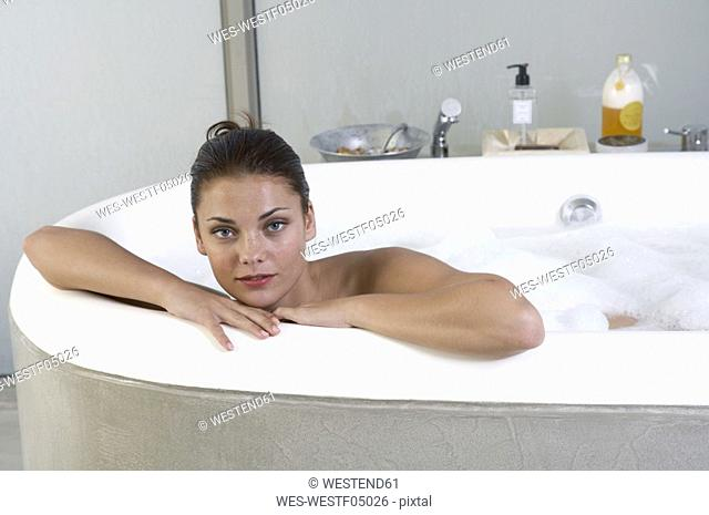 Youg woman ling in bath tub, looking to camera