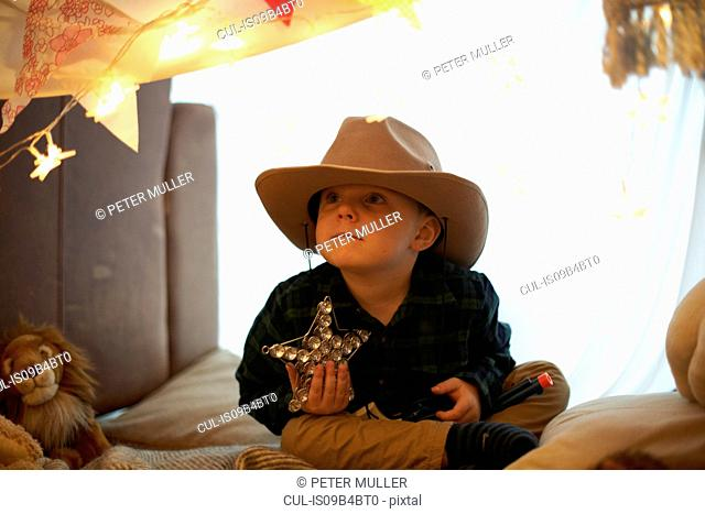 Portrait of cute boy in cowboy hat holding star in bedroom den