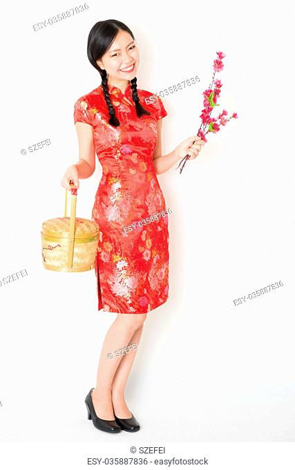 Oriental female in red qipao holding gift basket