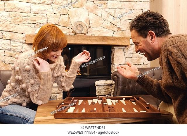 Couple playing backgammon, fireside in background