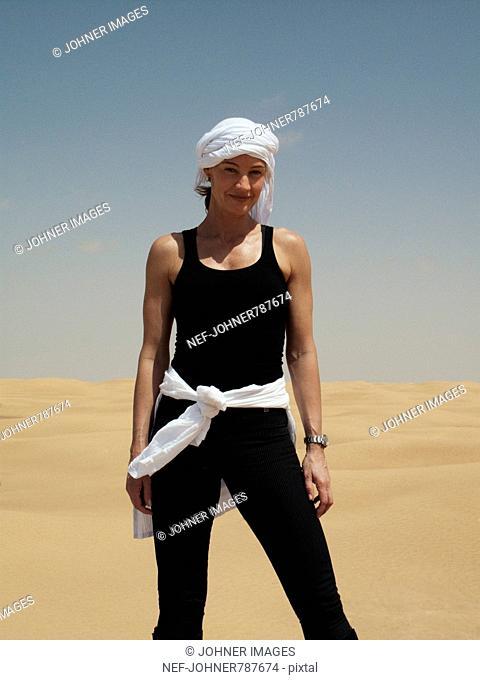 Woman wearing a turban in the desert, Tunisia
