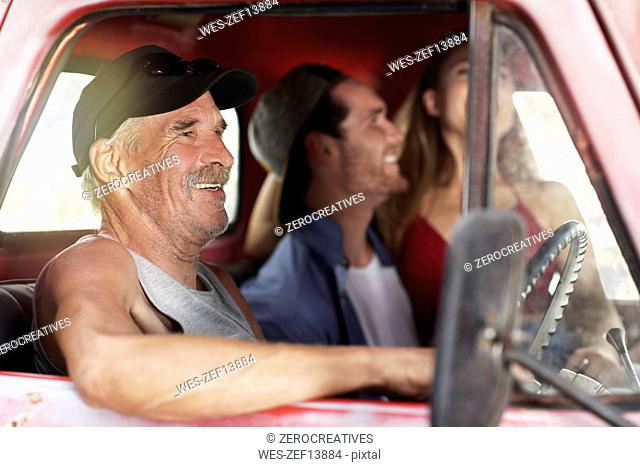 Happy senior man and young couple in an old pick up