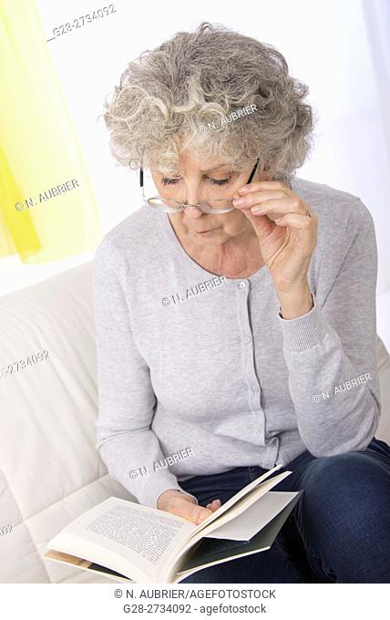 Senior woman sitting on her sofa, peacefully reading a book, her spectacles on her nose