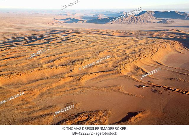 Farmhouse at the foot of a large grass-grown dune at the edge of the Namib Desert, aerial view from a hot-air balloon, NamibRand Nature Reserve, Namibia
