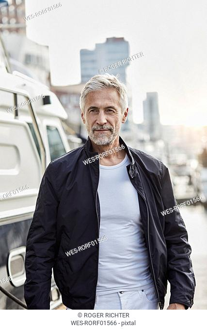 Confident mature man at a marina next to a yacht