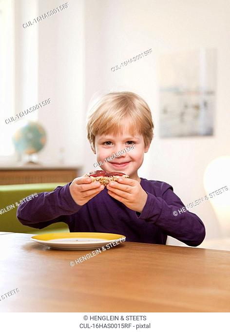 boy eating bread roll