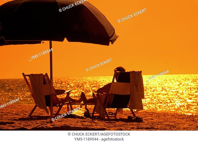 Beach Umbrella and Couple relaxing in lounge chairs. Captiva Island, Florida, USA