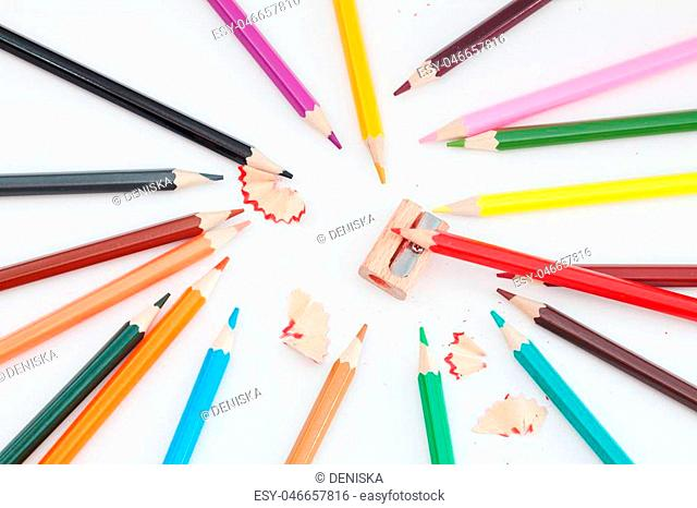 Colored pencils and sharpener on white. Photos school supplies