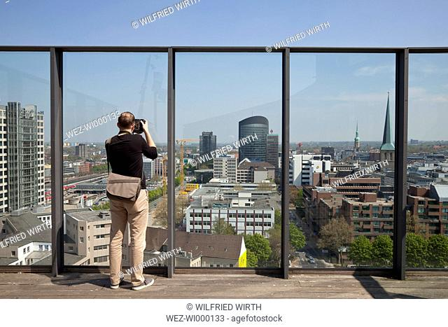 Germany, North Rhine Westphalia, Dortmund, tourist looking from panorama terrace of Dortmund U-Tower at the city