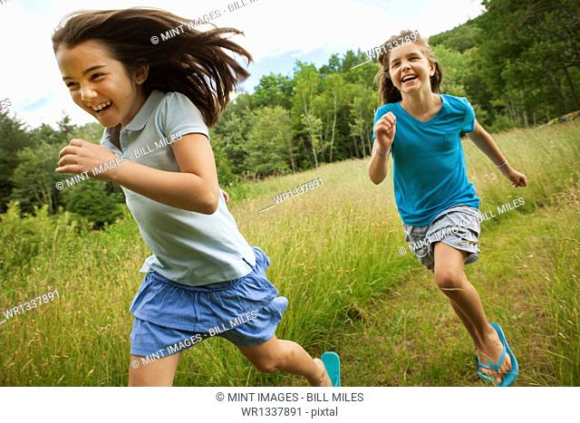 Two children, girls running and playing chase, laughing in the fresh air