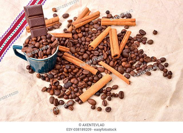 Cup of coffee with cinnamon sticks, bar of chocolate on vintage texture. Roasted coffee beans on jute background. Morning pleasures. Selective focus