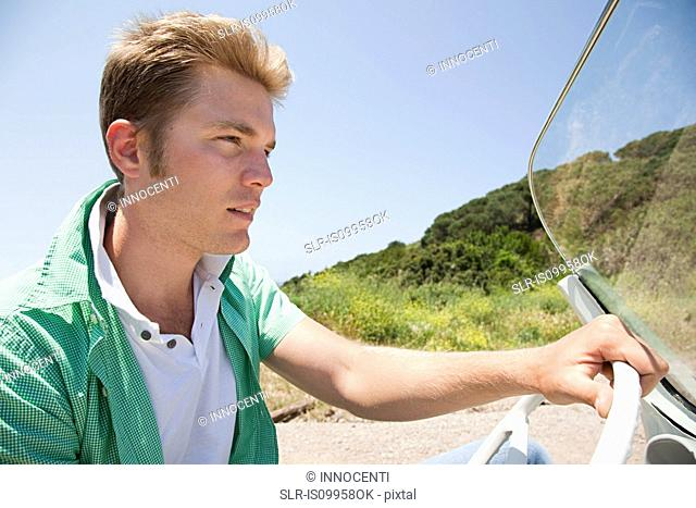 Young man driving convertible car