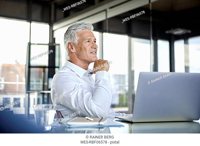 Businessman sitting in office, thinking