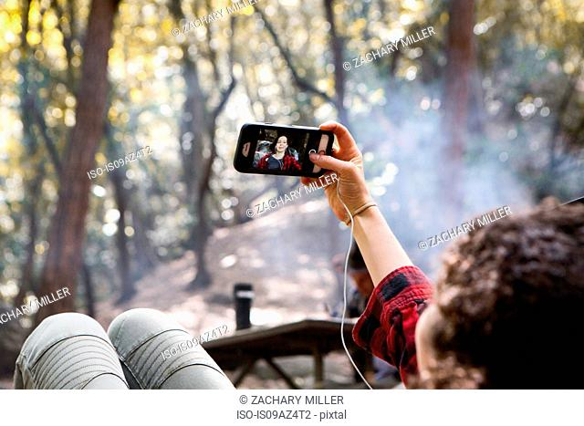 Over shoulder view of young female hiker taking smartphone selfie in forest, Arcadia, California, USA