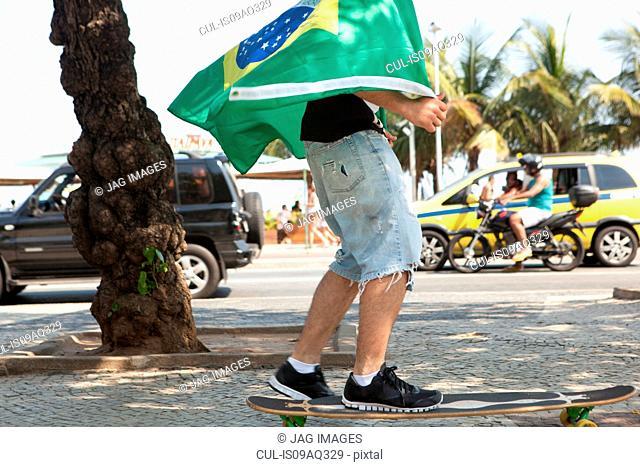 Young man skateboarding wrapped in Brazilian flag, Copacabana, Rio De Janeiro, Brazil