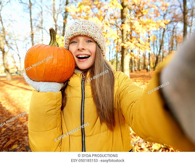 girl with pumpkin taking selfie at autumn park