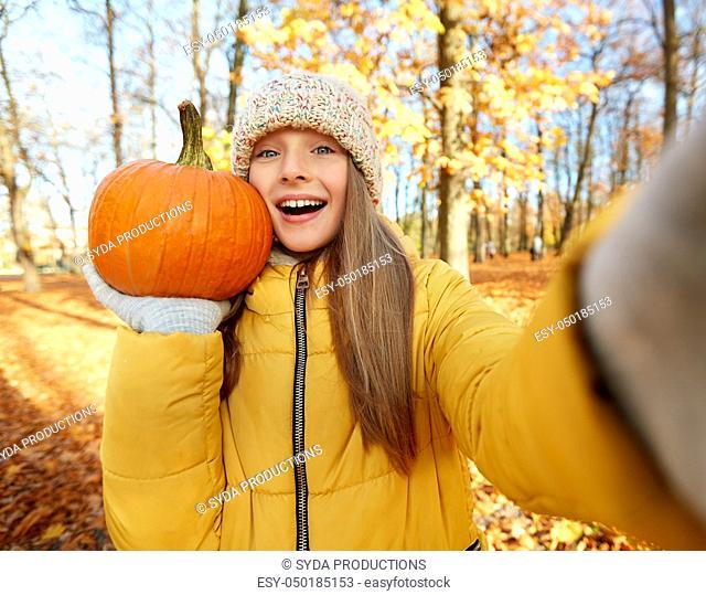 girl with pumpkin taking selfie at autumn park
