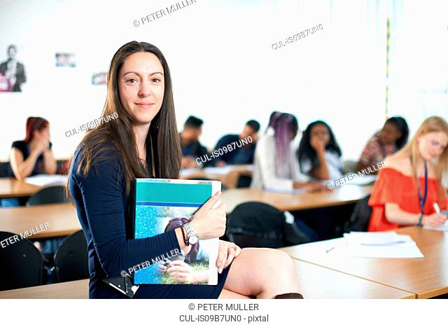 Portrait of teacher in classroom holding textbook looking at camera smiling