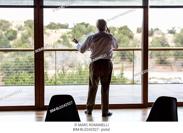 Caucasian businessman talking on cell phone near window