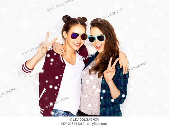 winter, christmas, people, fashion and gesture concept - happy smiling pretty teenage girls or friends in sunglasses showing peace hand sign over gray...