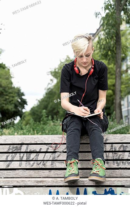 Young woman drawing on park bench