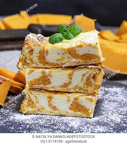 stack of square pieces of baked cheesecake cottage cheese with pumpkin sprinkle with powdered sugar