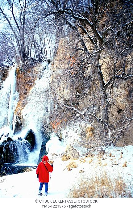 Young boy hiking near frozen waterfall in Colorado
