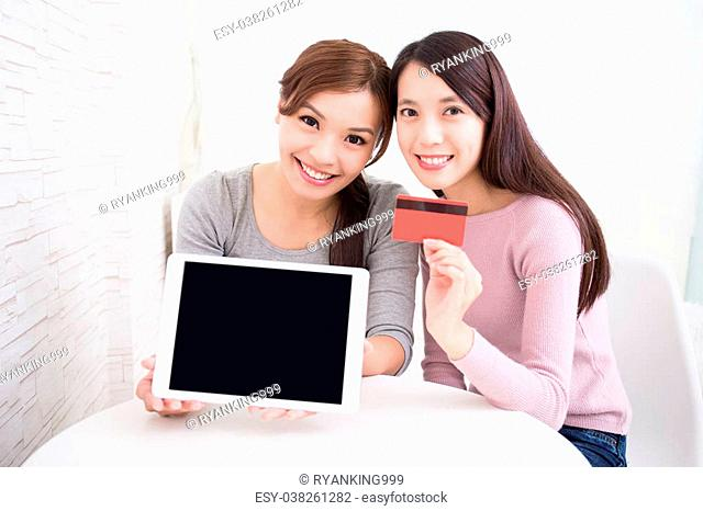 Two happy young female friends show empty digital tablet pc and credit card, great for your design, asian beauty