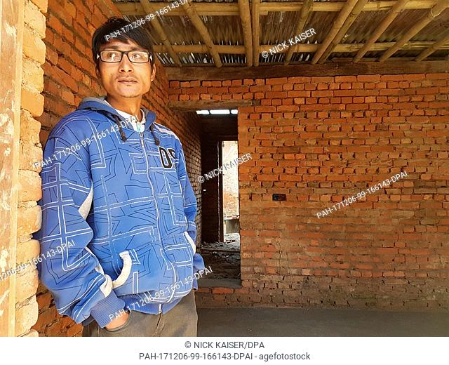 Rakesh Bada stands in the entrance of a house, which he built from his savings, in Bungamati, a suburb of Kathmandu, Nepal, 05 December 2017