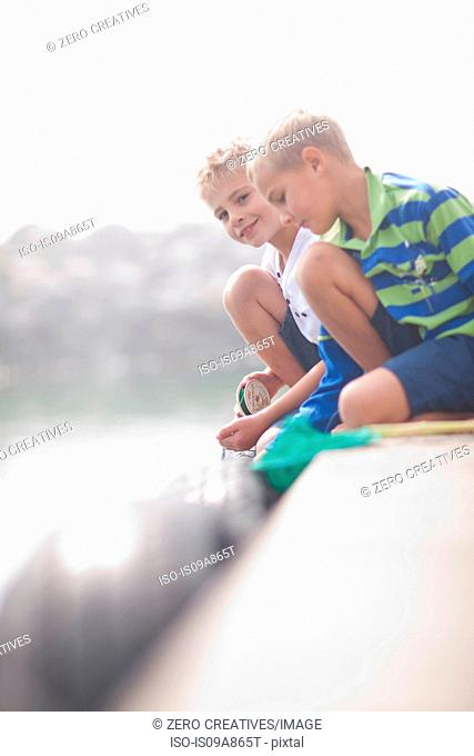 Close up of two young boys fishing on pier