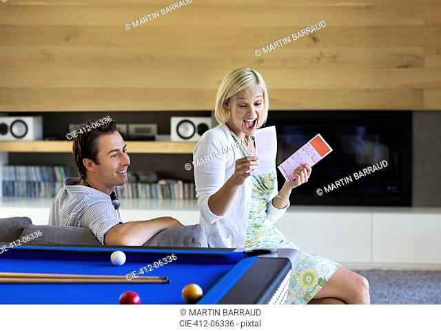 Couple checking lottery tickets on sofa