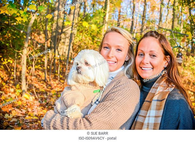 Portrait of young woman with mother and dog in woods