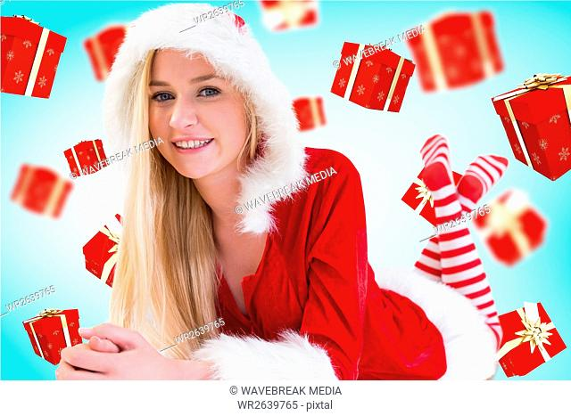 Beautiful woman in santa costume lying against digitally generated background