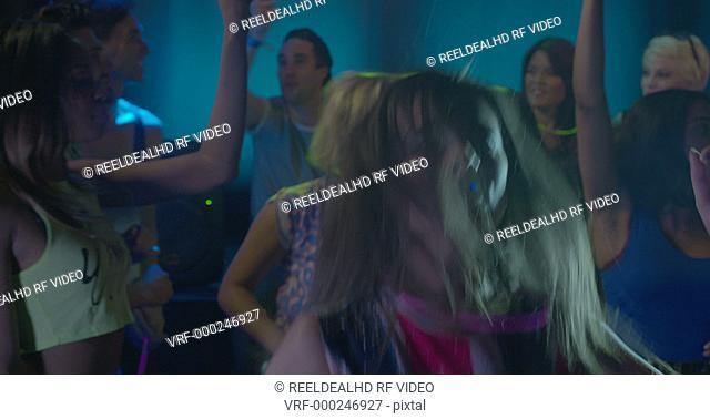 Woman dancing with friends and having fun in nightclub