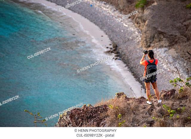 Woman taking picture on hilltop, Padar Island (Pulau Padar) within Komodo archipelago, Nusa Tenggara Timur, Indonesia