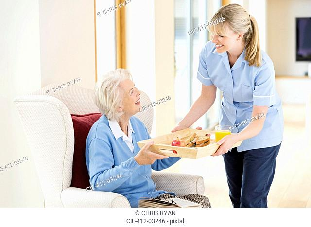 Caregiver giving older woman tray of food