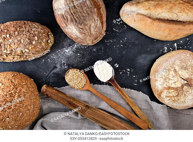 baked different loaves of bread on a black background, empty space in the middle, top view