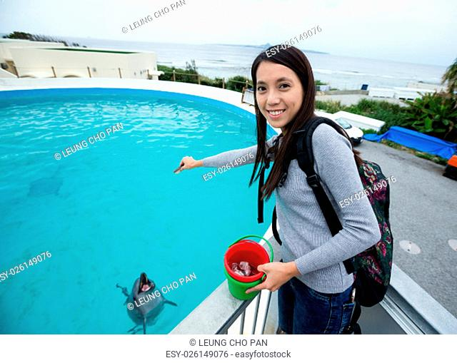 Young Woman feeding dolphin in aquarium