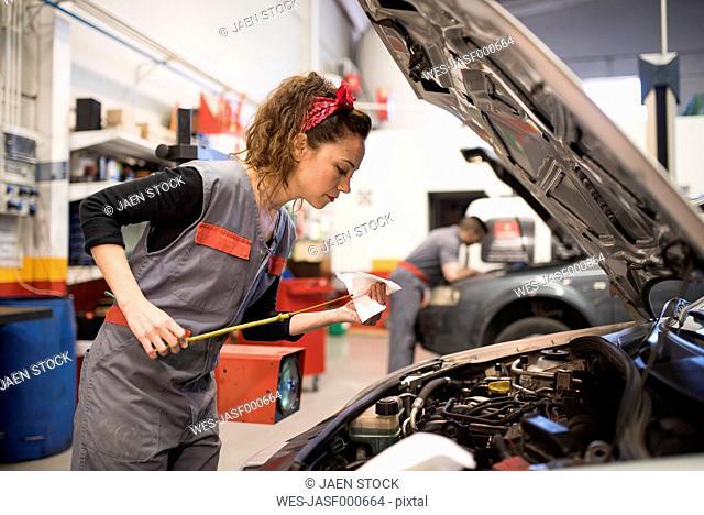 Mechanics working in workshop, checking oil level