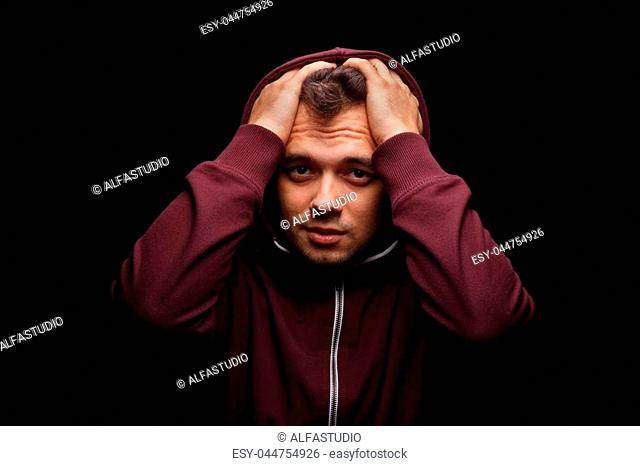 Shocked, surprised young man wearing a dark red hoodie on a black background. Sad, confused, lost student suffering with anxiety