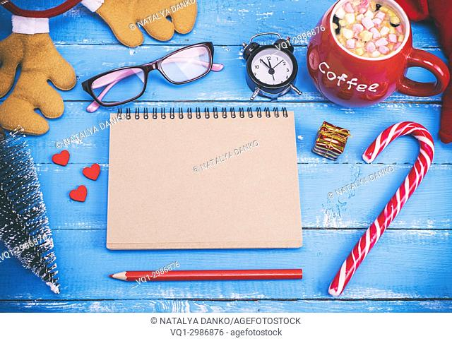 notebook with empty brown pages and hot chocolate in a red ceramic cup on a blue wooden table, top view