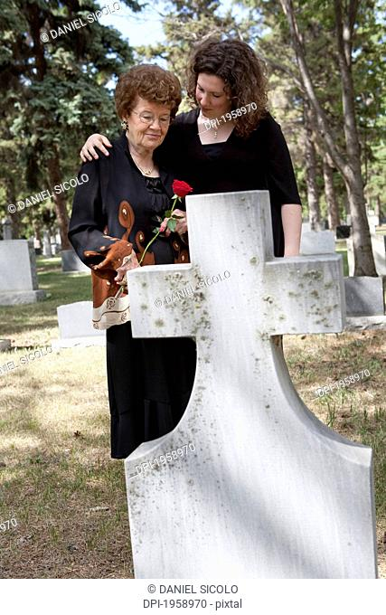 A Grandmother And Granddaughter Visiting A Grave In A Cemetery; Edmonton, Alberta, Canada