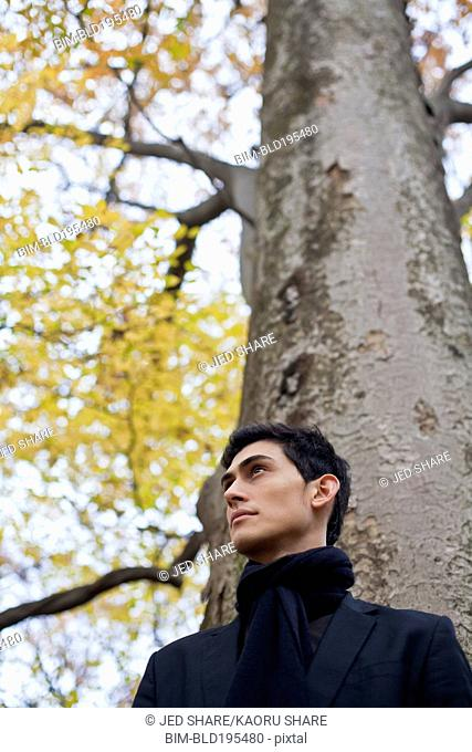 Pensive mixed race man standing under autumn tree