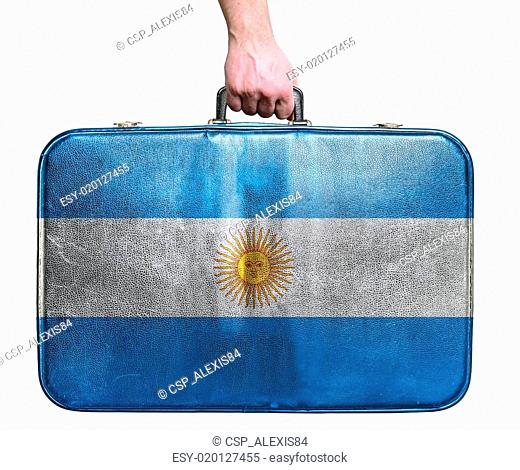 Tourist hand holding vintage leather travel bag with flag of Argentina