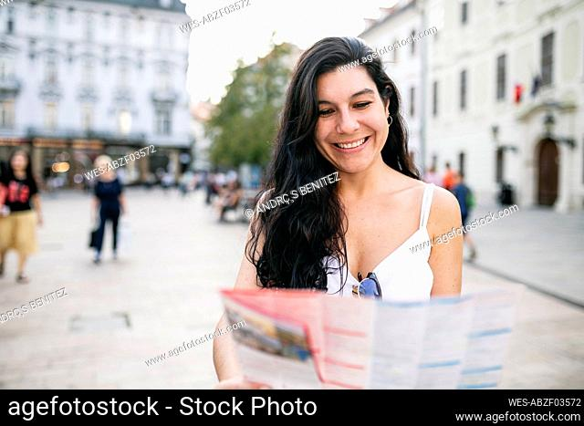 Tourist smiling while reading map on footpath