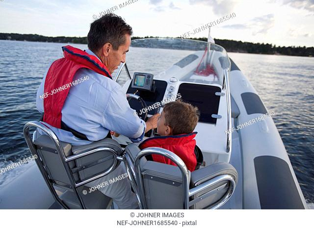 Father with son driving motorboat