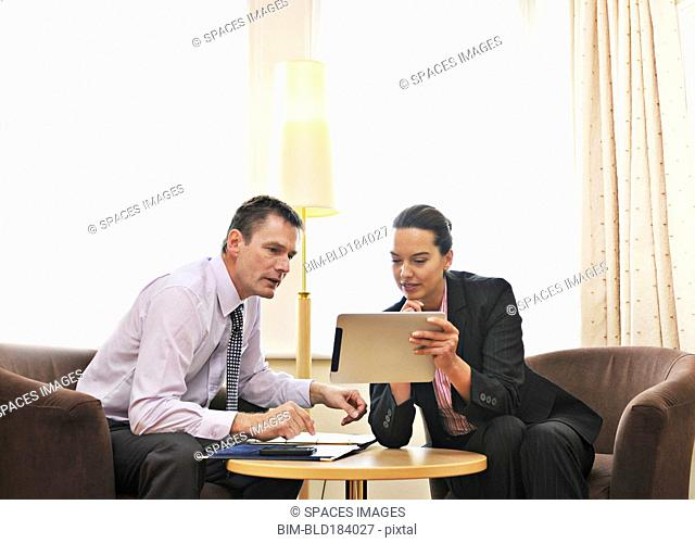 Caucasian business people using digital tablet in lounge