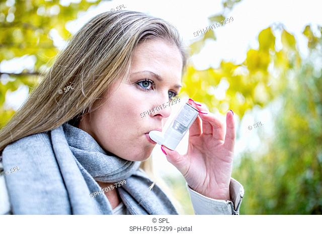 MODEL RELEASED. Young woman using asthma inhaler, close-up