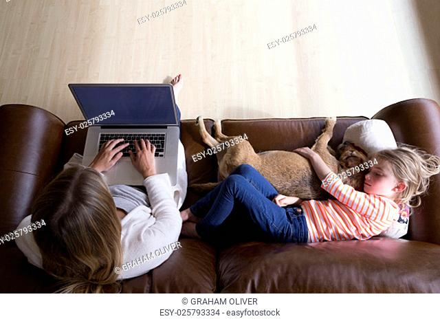 Ariel view of a woman using a laptop whilst her daughter is sleeping next to her, cuddling their pet dog
